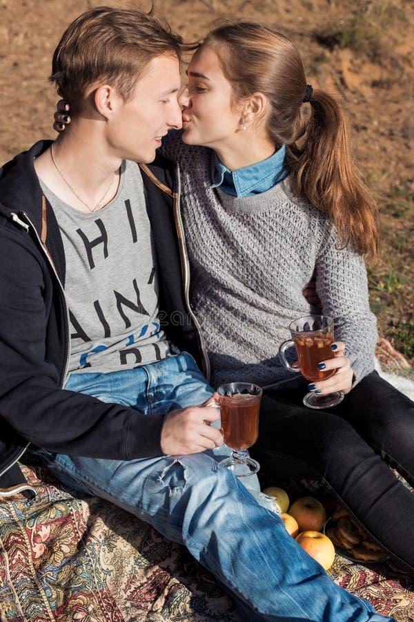 Красивые молодые счастливые пары в влюбленности сидя на озере подпирают на теплом солнечном вечере целуя и выпивая теплый чай стоковое изображение rf