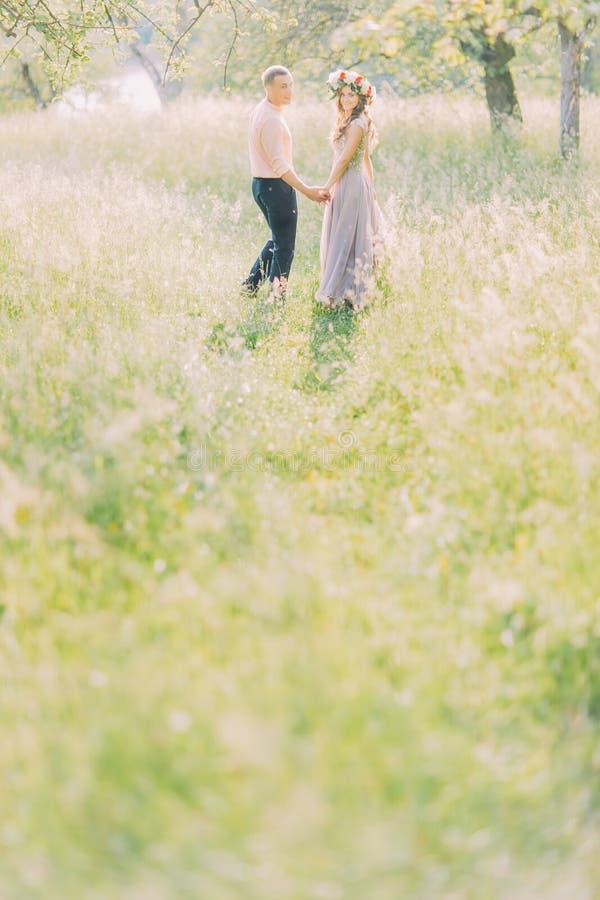 Красивые молодые любящие пары обнимая в весне цветения садовничают Романтичное датировка стоковое фото