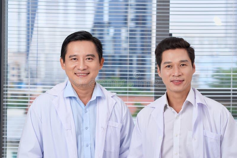 Красивые мужские доктора или медсестры стоя внутри здания больницы стоковое фото rf