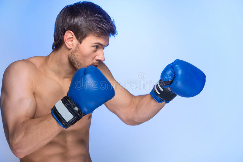 Красивые мышечные перчатки бокса молодого человека нося стоковая фотография rf