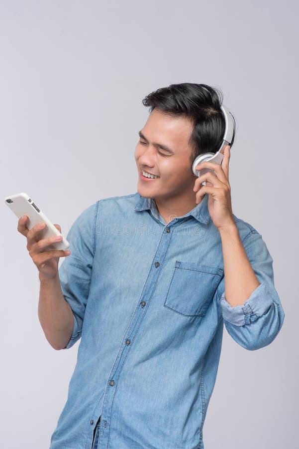 Красивые наушники молодого человека нося и мобильный телефон w держать стоковое фото rf