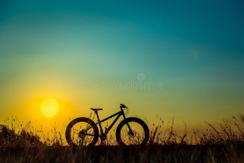 Красивые небо захода солнца и силуэт горного велосипеда стоковое фото rf