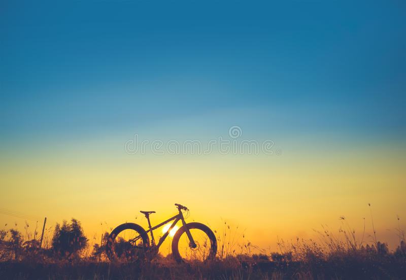 Красивые небо захода солнца и силуэт горного велосипеда стоковая фотография rf
