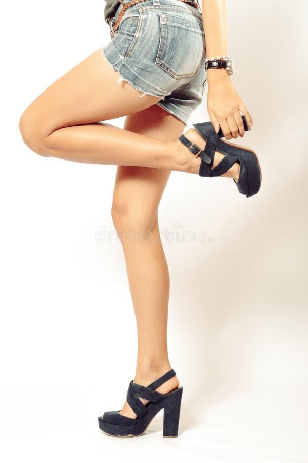 Красивые ноги взгляда со стороны молодой женщины в высокой пятке обувают съемку студии стоковые фото