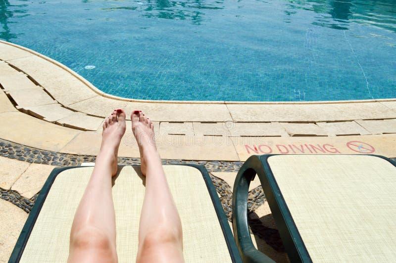 Красивые ноги, ноги девушек, женщины с красным маникюром на фоне deckchair и бассейн на тропическом теплом экзотическом взморье стоковые изображения rf