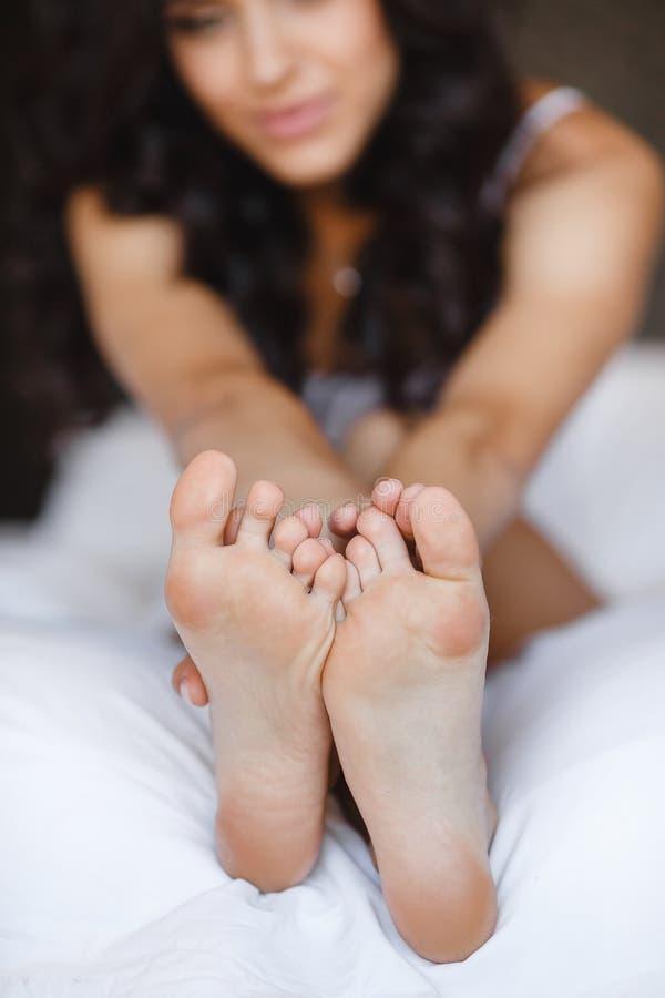 Красивые ноги, лежа в кровати молодой женщины стоковое изображение rf
