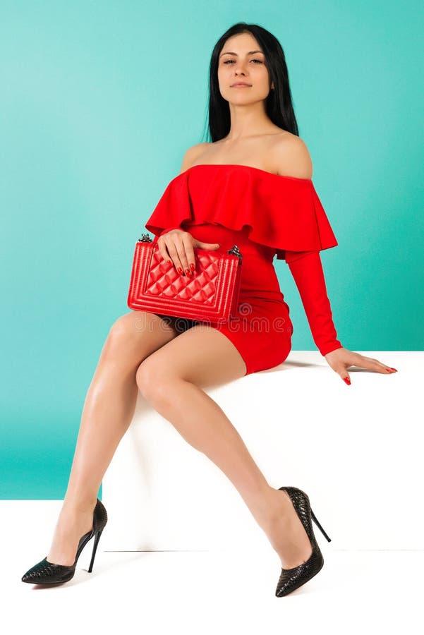 Красивые ноги женщины в красном платье с сумкой с туфлями на высоких каблуках, сидящими на белой скамье. стоковое фото