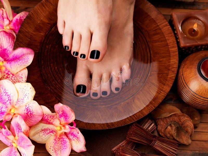 Красивые ноги женщин с черным pedicure после курорта стоковое изображение rf