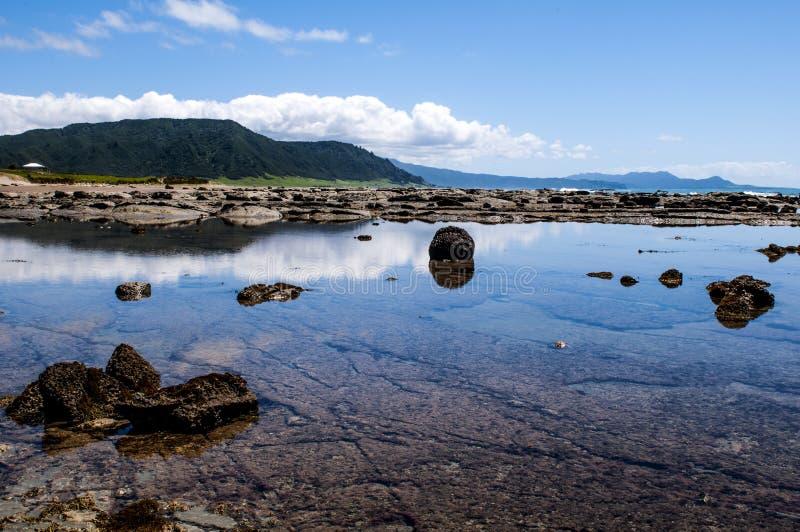 Красивые отражения на пляже вдоль восточной дороги накидки, Новой Зеландии стоковое изображение rf