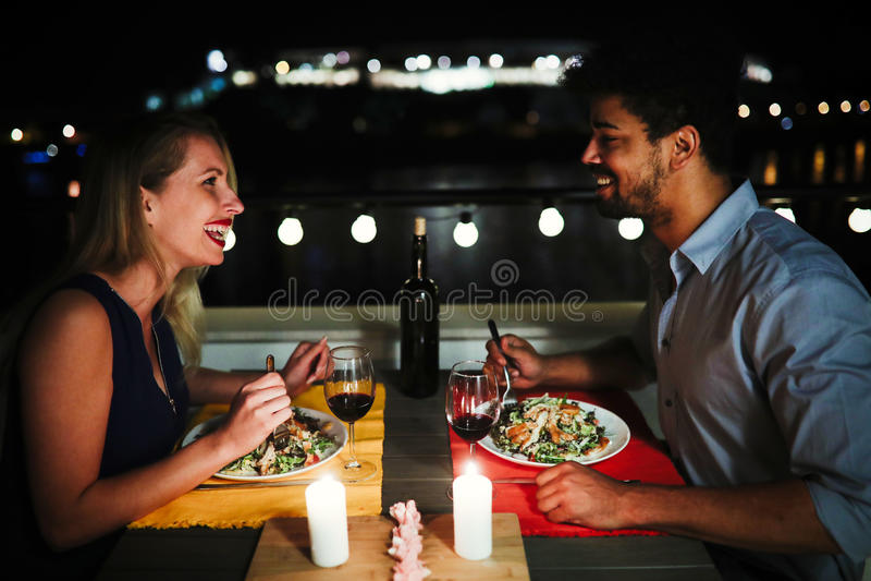 Красивые пары в влюбленности имея романтичный обедающий на ноче стоковые изображения
