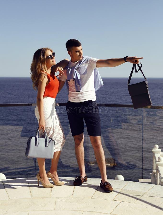 Красивые пары в элегантных одеждах при сумки представляя в лете паркуют стоковые изображения