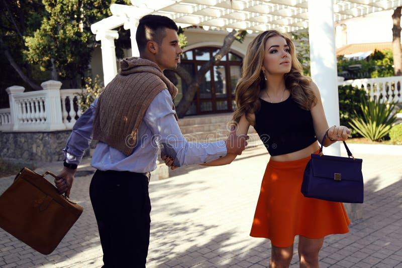 Красивые пары в элегантных одеждах при сумки представляя в лете паркуют стоковая фотография