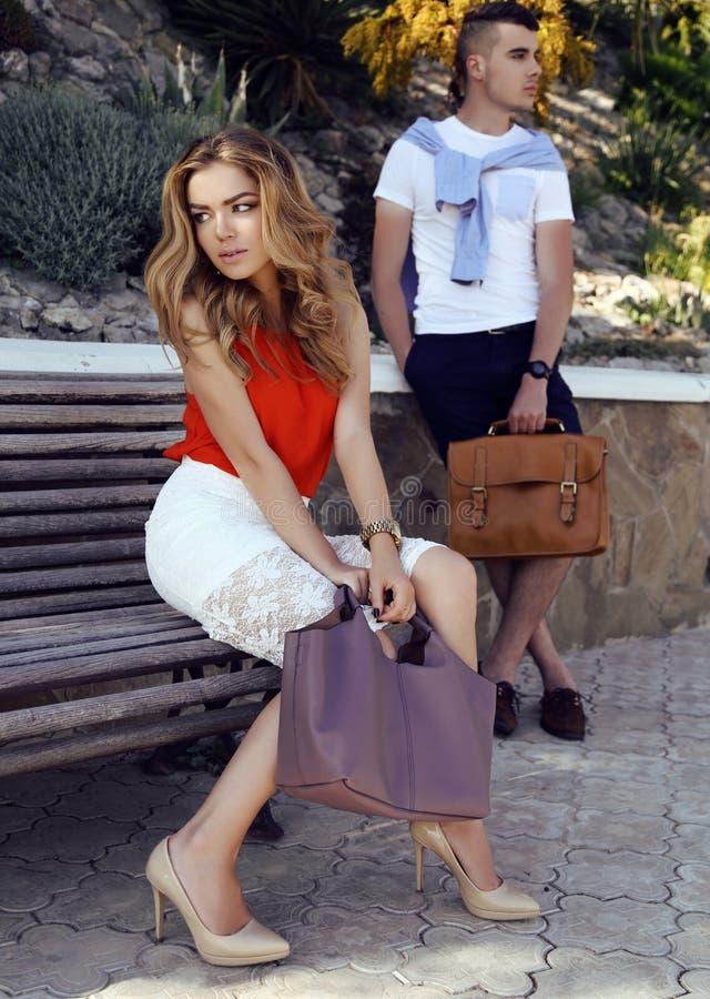 Красивые пары в элегантных одеждах при сумки представляя в лете паркуют стоковые фото
