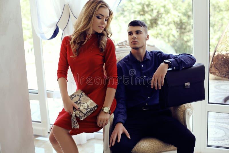 Красивые пары в элегантных одеждах при сумки представляя в интерьере стоковое изображение rf