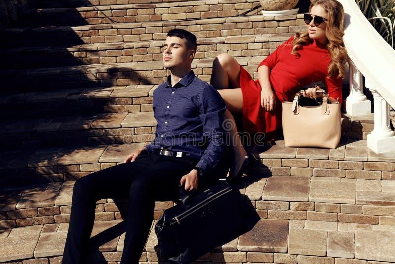 Красивые пары в элегантных одеждах при сумки представляя на лестницах стоковые фотографии rf