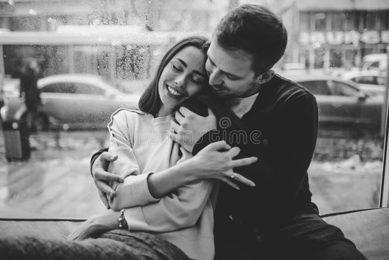 Красивые пары Любя парень обнимает его очаровательную девушку сидя на windowsill в уютном кафе r стоковые изображения