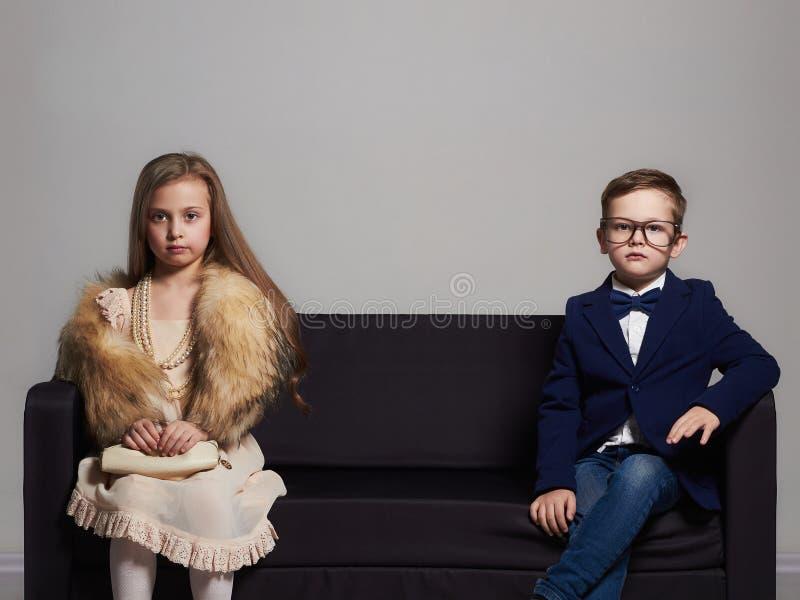 Красивые пары на кресле маленькая девочка и мальчик красоты ягнит стильное стоковая фотография
