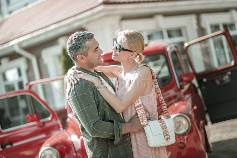 Красивые пары обнимая перед их автомобилем стоковое фото rf