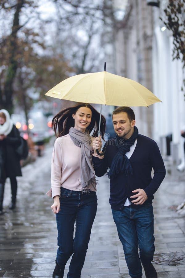 Красивые пары, парень и его девушка одетые в случайных одеждах бегут под зонтиком на улице в стоковое изображение rf
