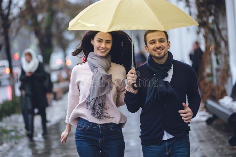 Красивые пары, парень и его девушка одетые в случайных одеждах бегут под зонтиком на улице в стоковые фотографии rf
