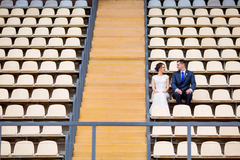 Красивые пары сидя на стойке футбольного стадиона стоковое изображение