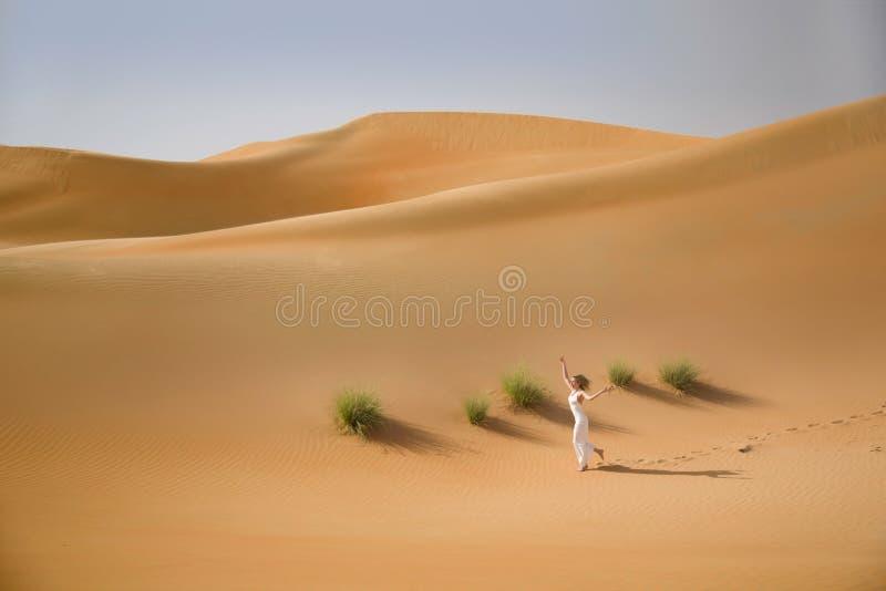 Красивые песчанные дюны, трава и тонкая идущая женщина в белом платье стоковая фотография rf