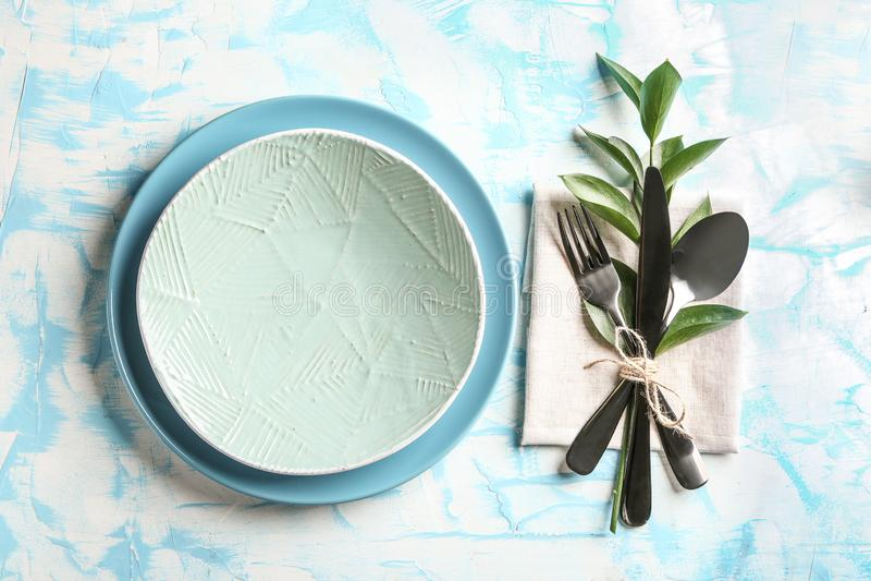 Красивые плиты и flatware на таблице цвета стоковое фото
