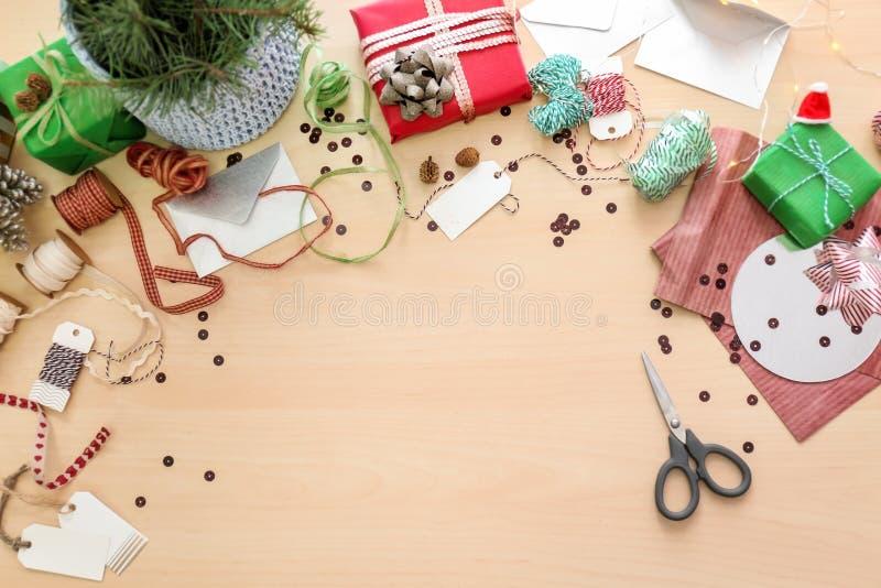Красивые подарочные коробки рождества и материалы упаковки на светлой таблице стоковое изображение rf