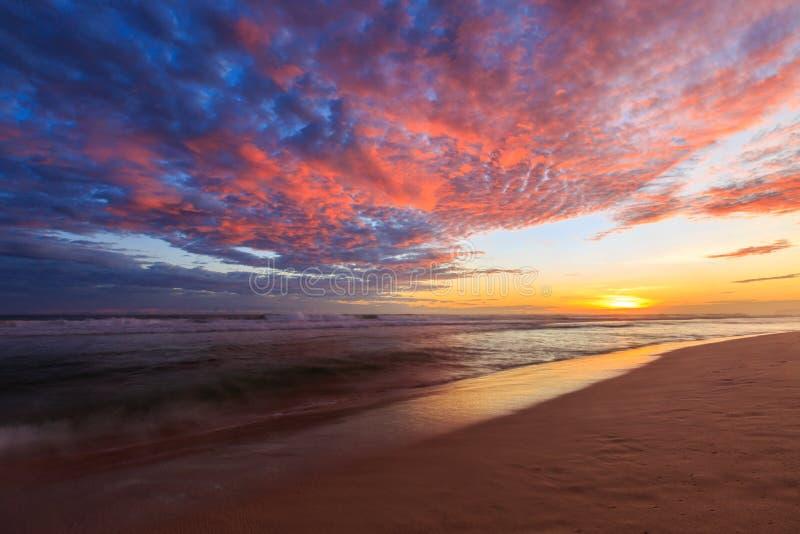 Красивые покрашенные облака на пляже на заходе солнца стоковые фото