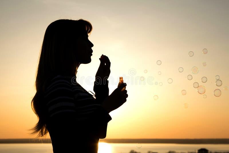 Красивые пузыри дуновения маленькой девочки на природе стоковые фото