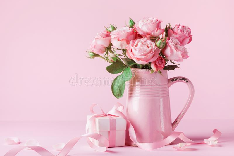 Красивые розовые цветки в розовых вазе и подарочной коробке для поздравительной открытки дня женщин или дня матерей стоковое изображение rf
