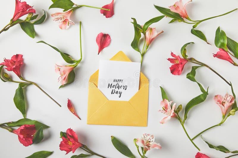 красивые розовые цветки и счастливая поздравительная открытка дня матерей на сером цвете стоковые фотографии rf