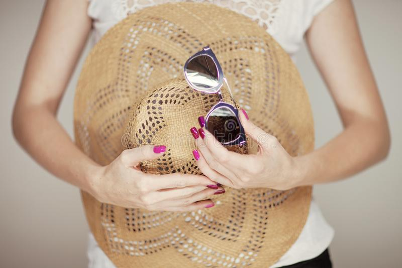 Красивые руки женщины при совершенный розовый маникюр держа sunhat и солнечные очки, счастливое настроение пляжа стоковые изображения