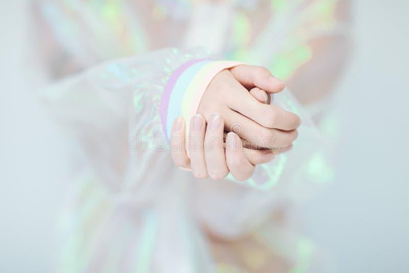 Красивые руки и оружия женщины нося свитер с голографическим влиянием, взглядом современного авангарда искусственным пластичным стоковые изображения