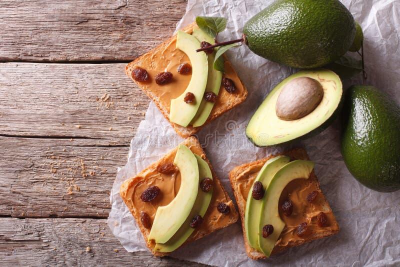Красивые сандвичи с авокадоом, арахисовым маслом и изюминками стоковая фотография