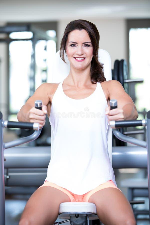 Красивые сексуальные пары человека женщины делают разминку в спортзале fitnes - прессе комода, стенде стоковая фотография