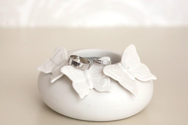 Красивые серебряные обручальные кольца на нежном фарфоре вычисляют стоковое изображение