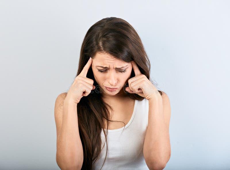 Красивые серьезные сконцентрированные пальцы женщины 2 держа сторону и думая и смотря вниз в белой рубашке и длинных волосах стоковая фотография