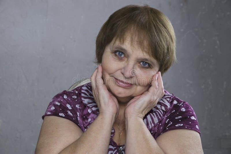 Красивые старшие голубые глазы женщины Милый взрослый касаясь ее стороне стоковое изображение