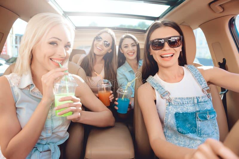 Красивые стильные девушки смотря смеяться над камеры стоковое изображение