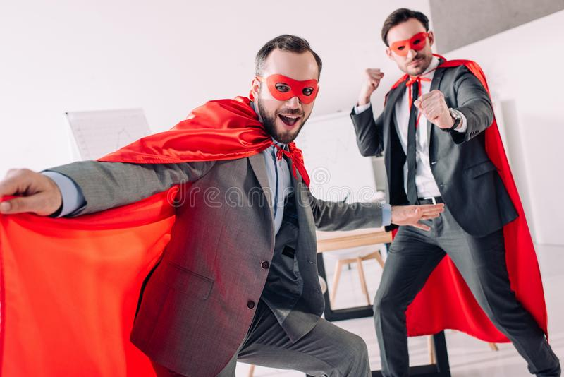 красивые супер бизнесмены в масках и накидки имея потеху стоковая фотография rf