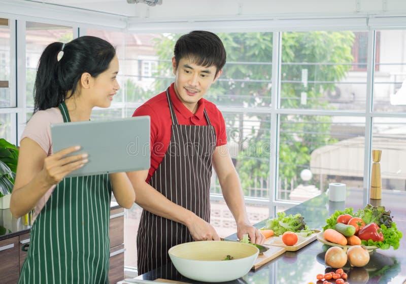 Красивые счастливые азиатские пары варят в кухне подготовьте еду салата для обедающего Человек и женщина усмехаясь смотрящ меню о стоковое фото