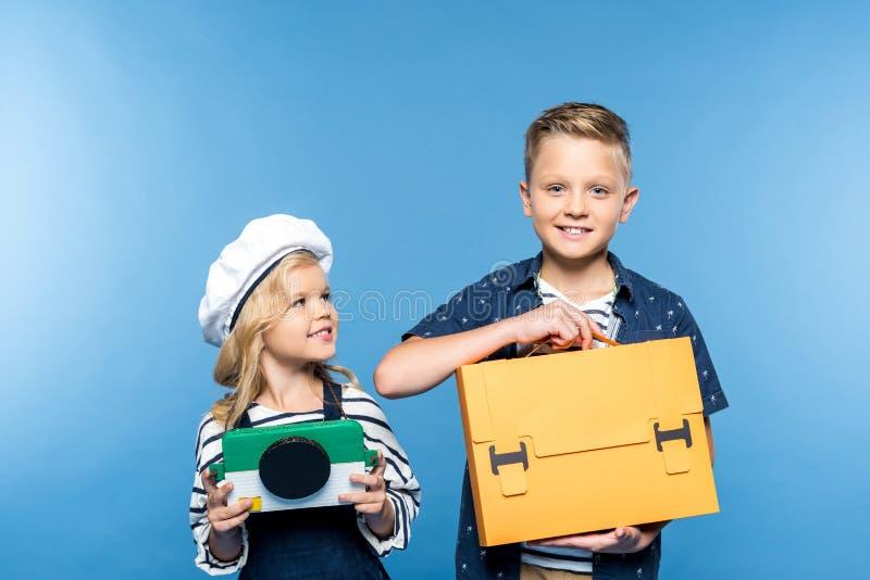 красивые счастливые дети держа камеру и портфель стоковые изображения