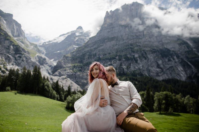 красивые счастливые молодые пары свадьбы обнимая на зеленом луге горы стоковая фотография rf