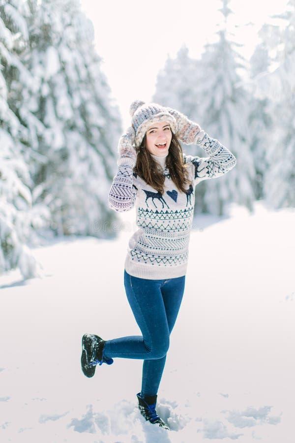 Красивые счастливые смеясь перчатки и шарф шляпы зимы молодой женщины нося покрытые с хлопьями снега Backgro ландшафта леса зимы стоковое фото rf
