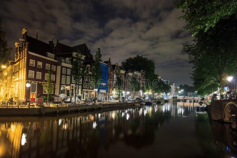 Красивые традиционные старые здания на ноче вдоль канала с отражением на воде в Амстердаме, Нидерландах стоковое фото