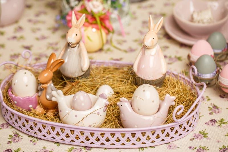 Красивые украшения пасхи пастельные с сервировкой стола Кролики фарфора и пасхальные яйца стоковое фото rf
