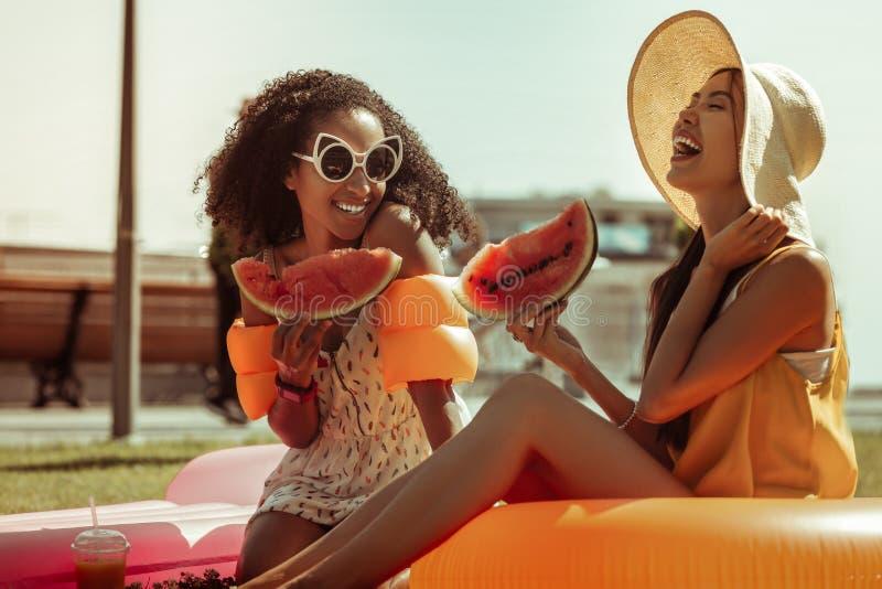 Красивые умоляющие темн-с волосами дамы сидя с арбузом в руках стоковая фотография rf