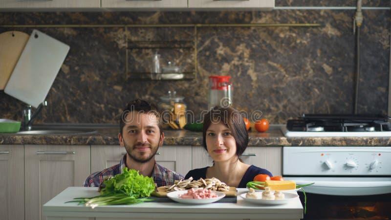 Красивые усмехаясь пары над таблицей с овощами пока варящ в кухне стоковое изображение