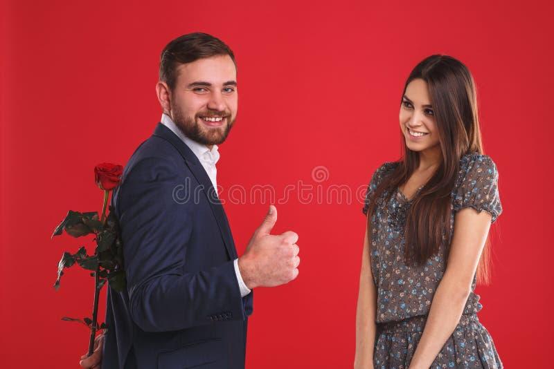 Красивые усмехаясь пары с красной розой на красной предпосылке стоковая фотография rf
